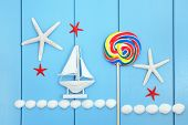 Sea shell, lollipop candy and decorative sailing boat abstract over wood background.