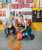 stock photo of air compressor  - Full length portrait of saleswoman assisting male customer in using air compressor at hardware store - JPG