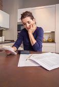 stock photo of unemployed people  - Unemployed and divorced woman with many debts reviewing her monthly bills - JPG