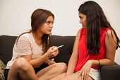 picture of teen pregnancy  - Concerned Hispanic teenager confiding on her best friend about her pregnancy - JPG