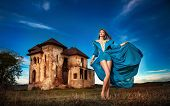foto of cloudy  - Fashionable beautiful young woman in long blue dress posing with old castle and cloudy dramatic sky in background. Attractive long hair brunette girl with elegant luxurious dress, outdoors shot. ** Note: Soft Focus at 100%, best at smaller sizes - JPG