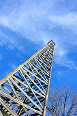 stock photo of derrick  - Rustic wooden oil derrick is framed by blue sky and whispy clouds - JPG