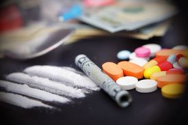 image of methadone  - lines of cocaine beside a wrapped up dollar bill and narcotic pills  - JPG