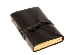 picture of leather-bound  - An old fashioned leather bound blank journal closed with cord wrapped around it shot over white - JPG