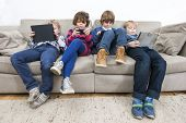 stock photo of boredom  - Brothers and sister using electronic devices while slouching on sofa at home - JPG