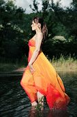 picture of undine  - Beautiful water nymph walking on the water in orange gown - JPG