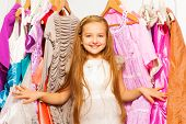 foto of clothes hanger  - Smiling girl standing among colorful bright dresses and clothes on hangers during shopping - JPG