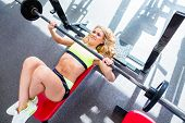 pic of bench  - Woman at bench press in gym exercising for better fitness - JPG