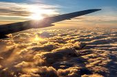 picture of mountain-high  - View of golden sunrise outside airplane window with deliberate lens flare over plane wing silhouette for effect - JPG
