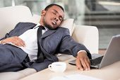 image of sleeping  - Young African business man is holding hand on laptop keyboard while sleeping on the couch - JPG