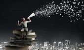 foto of trumpets  - Young man sitting on pile of books and screaming in trumpet - JPG