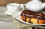 picture of eclairs  - Tasty eclairs and cup of tea on wooden table - JPG