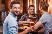picture of foreground  - Handsome young man toasting with beer and smiling while sitting with his friends in beer pub - JPG