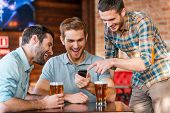 stock photo of casual wear  - Three happy young men in casual wear drinking beer in pub while one of them pointing smart phone and smiling - JPG