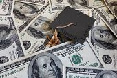 foto of graduation  - Miniature graduation cap with Student Loans text on assorted cash - JPG
