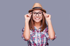 stock photo of shot glasses  - Portrait of beautiful young woman in glasses and funky hat adjusting her glasses and smiling while standing against grey background - JPG