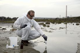 image of groundwater  - Worker in a protective suit examining pollution in the water at the industry.