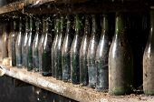 image of wine cellar  - Old unlabeled dusty wine bottles on a cellar shelf in a concept of wine making and viticulture - JPG