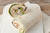 picture of sandwich wrap  - sandwich wrap or tortilla with leftover meat cheese and lettuce on wooden background - JPG