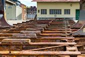 pic of shipyard  - Detail of the old and rusty machinery a disused shipyard ramp - JPG