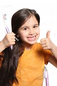 foto of child missing  - Little seven year old girl shows big smile showing missing top front teeth and holding a toothbrush and thumbs up on a white background - JPG