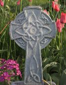 image of celtic  - A Celtic Cross stands among garden flowers and tulips - JPG