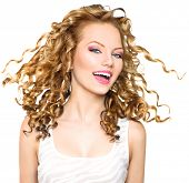 stock photo of blowing  - Beauty model girl with blowing Blonde curly hair - JPG