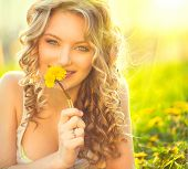 stock photo of allergy  - Beauty blond model girl lying on a field and smelling dandelion flowers - JPG