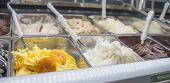 foto of flavor  - Fresh mandarine ice cream and other flavors on the bench of an ice - JPG