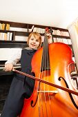 picture of cello  - View from below of happy small girl in school uniform dress playing on the cello sitting near the piano and shelves with books - JPG