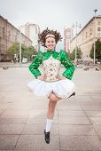 picture of wig  - Young woman in irish dance dress and wig dancing outdoor - JPG