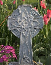 picture of celtic  - A Celtic Cross stands among garden flowers and tulips - JPG