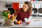 Постер, плакат: Woman In Kitchen Holding Shopping List Looking Through Items