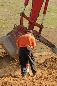 picture of vibration plate  - Commercial development building contractor working on building site installing a retaining wall moving dirt for the lift - JPG
