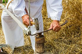 picture of scythe  - Man with hammer and iron tool on the tree stump is sharpening his scythe - JPG