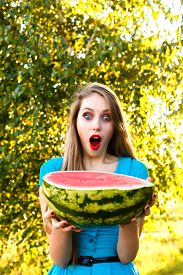 picture of cucurbitaceous  - Beautiful young girl stares at the half of juicy watermelon - JPG