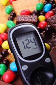 Постер, плакат: Glucometer With Heap Of Sweets And Cane Brown Sugar Unhealthy Food