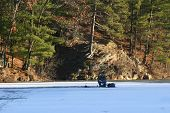 image of bluegill  - an ice fisherman sitting at his spot on the ice along a beautiful bank of woods and rocks.