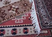stock photo of thrift store  - a turkish rug dealer displaying his lovely handmade carpets - JPG