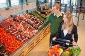stock photo of grocery store  - Smiling mid adult man pointing at vegetables while shopping with wife in grocery store - JPG