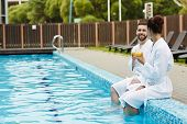 Young affectionate couple with drinks having talk while sitting by swimming pool with their legs in  poster