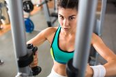 Confident athletic woman looking at camera while having intensive training on butterfly machine at m poster