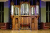 stock photo of pipe organ  - Massive wooden pipe organ with many metal pipes and ornate finishing - JPG