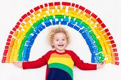 Child Playing With Rainbow Plastic Blocks Toy poster
