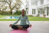 Front view of determined active senior Caucasian woman doing yoga on exercise mat in the porch at ho poster