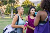 Group of multiethnic young women talking to each other after fitness exercising at park. Happy smili poster
