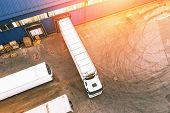 Aerial Photo Of Cargo Trucks In Industrial Warehouse Or Logistic Center Waiting For Loading Goods In poster