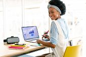 Front view of African american female graphic designer using graphic tablet while looking at laptop  poster