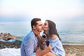 Romantic Romantic Couple Sitting With Wineglasses And Kissing At Seaside At Sunset. Romantic Concept poster
