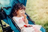 Cute Adorable Caucasian Toddler Baby Girl Sitting In Stroller Outside And Eating Berries Fruits. Fun poster